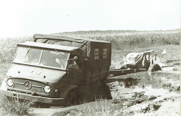 Dieser Unimog-S mit Radstand 2700 mm zieht einen  Anhänger durch den Schlamm