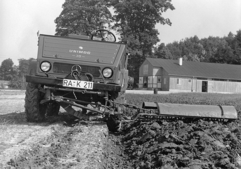 Unimog U30, Baureihe 411 mit Bodenfräse - im Hintergrund die frühere Unimog-Schulung