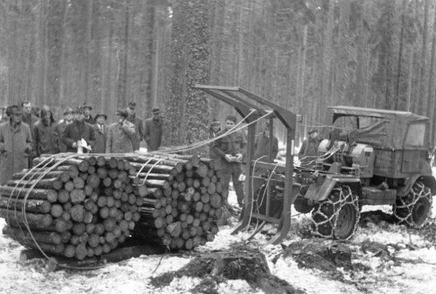 Unimog Baureihe 411 mit Forstausrüstung und Holzzange bei der Aufnahme von Kurzholzbündeln