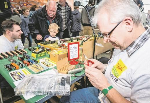 Während Ralf Nolde aus Lobberich ein selbst gefertigtes Ersatzteil in den Wagen einbaut, zeigt der Opa dem Enkel, wie man mit dem Trafo die Geschwindigkeit steuert. - Foto: Hegmann
